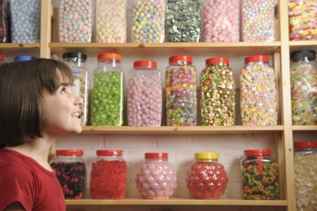 sweet shop: young girl smiling at camera in sweet shop