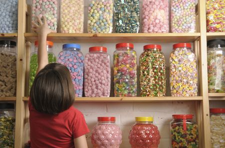 child reaching for sweet jar on top shelf Stock Photo