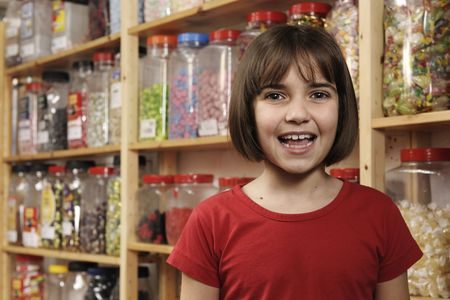 young girl smiling at camera in sweet shop   photo