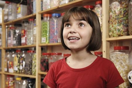 young girl smiling in awe at rows of sweets photo