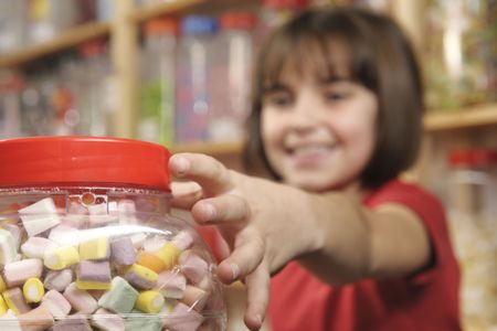 young girl grabbing a jar of sweets in shop photo