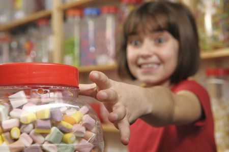 manic: young girl grabbing a jar of sweets in shop