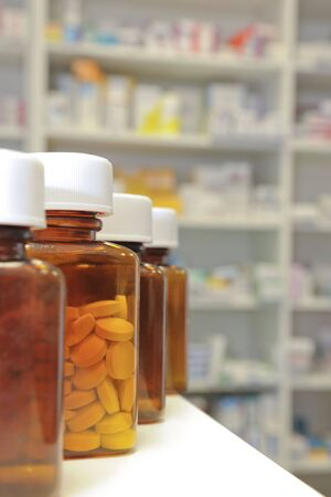 dispense: row of bottles and pills on a chemists counter Stock Photo