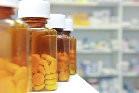 pills bottle: row of bottles and pills on a chemists counter Stock Photo