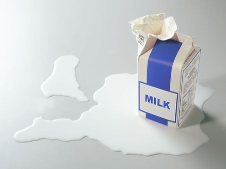 carton of milk opened with spilt milk around it