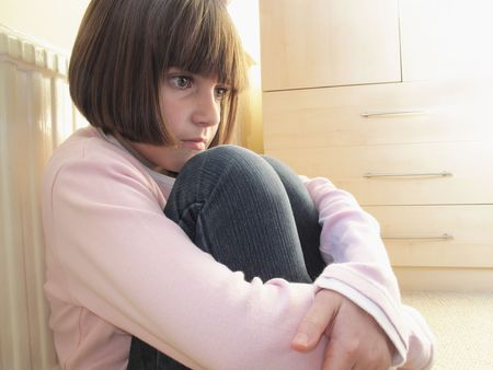 dismal: young girl sitting down with kness curled up looking depressed