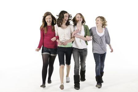 4 teenage girls linking arms walking towards camera smiling Stock Photo