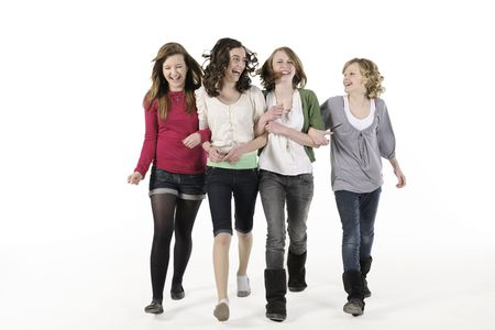 walk in: 4 teenage girls linking arms walking towards camera smiling Stock Photo