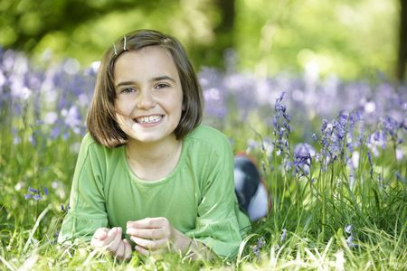 young girl lying in a wood full of bluebells Stock Photo - 6837702