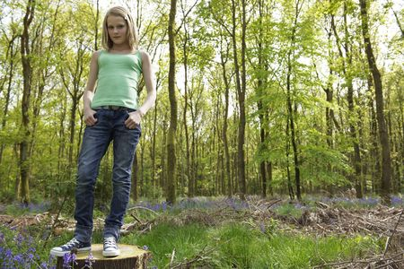 unrestricted: young girl standing in a forest enjoying the fresh air