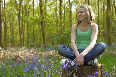 unrestricted: young girl sitting in a forest enjoying the fresh air Stock Photo