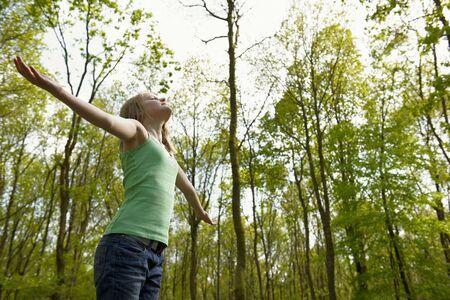 obudził: Dziewczynka mÅ'odych stojÄ…cych w lesie korzystajÄ…cym z Å›wieżym powietrzem