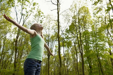 deliverance: young girl standing in a forest enjoying the fresh air