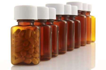 row of bottles with pills in the front container on white background