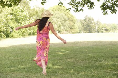young attractive woman walking away from camera with arms outstretched   Stock Photo