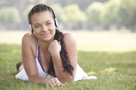 young attractive girl lying on grass wearing headphones while listening to music  photo