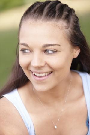 trenzas en el cabello: Retrato de joven atractiva sonriente con cabello trenzado  Foto de archivo