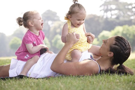 family tickle: mother playing with daughters in the park in summer