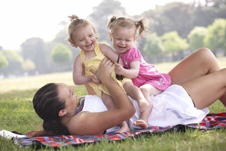 mother playing with daughters in the park in summer photo