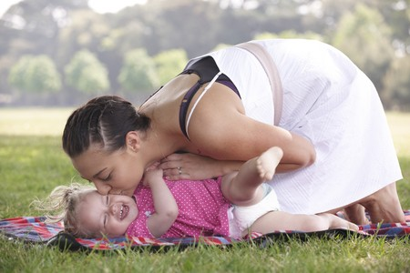 family tickle: mother playing and kissing with daughter in the park in summer