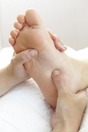 reflexologie plantaire: seul un pied se fait masser par paire de mains Banque d'images