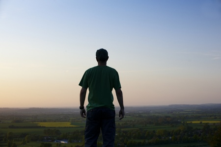 awakened: Man standing  in front of landscape at dusk