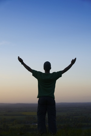 Man standing with arms outstretched in front of landscape at dusk Stock Photo
