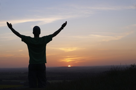 man with arms outstretched in front of sunset