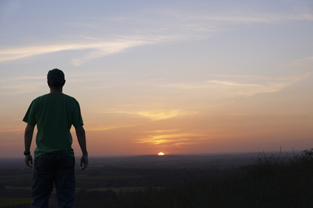 Man standing and looking at sunset on horizon