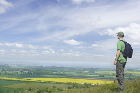 look for: Man standing looking at landscape with rucksack and his back and space for copy Stock Photo