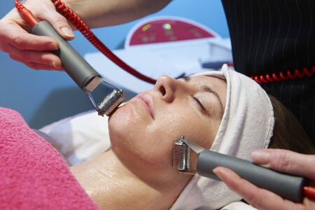 beauty treatment clinic: woman having a stimulating facial treatment from a therapist Stock Photo