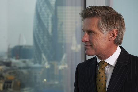 Portrait of a senior executive by a window smiling looking off camera Stock Photo