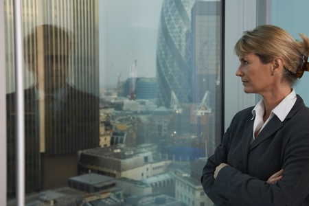Business woman looking out of window with reflection of business man looking back