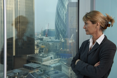 Senior business woman looking out of window with city of London in background
