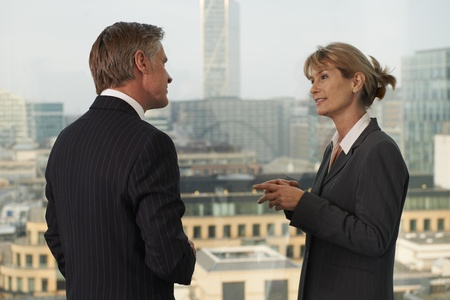 Senior business man and woman standing by window with city in background having a conversation