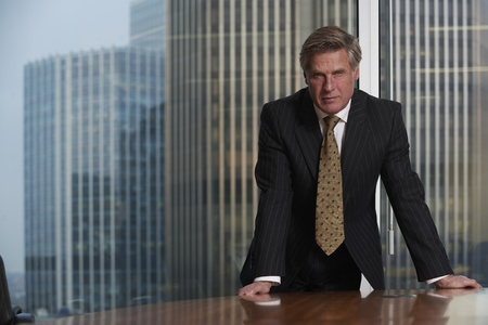 Business man leaning on table in boardroom looking at camera photo