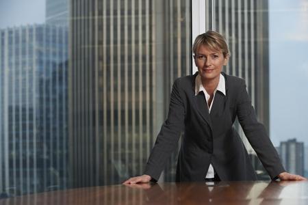 Mujer de negocios apoyándose en silla en la sala de juntas mirando la cámara Foto de archivo