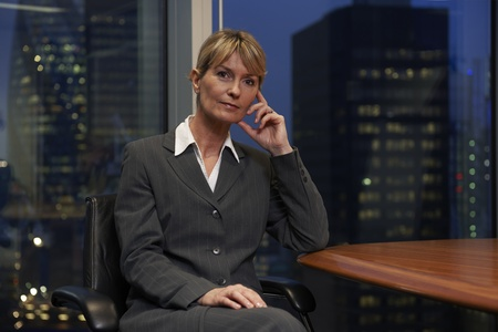 boardroom meeting: Business woman sitting at table in boardroom looking at camera