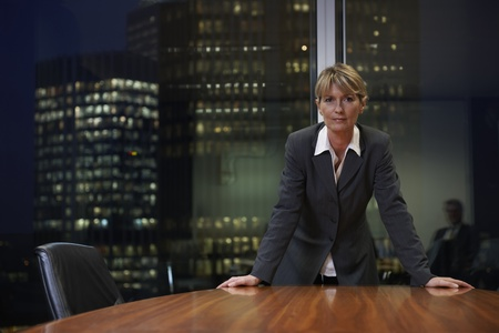 Senior Business woman leaning on table in boardroom looking at camera Stock Photo