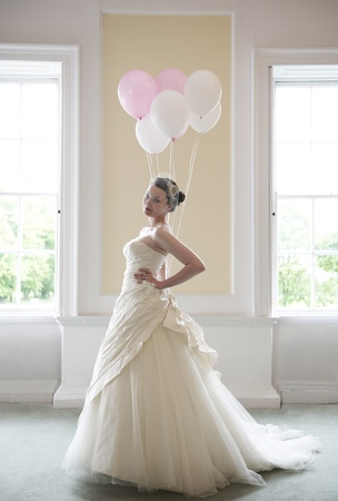 pretty bride in her wedding dress holding ballons in front of windows