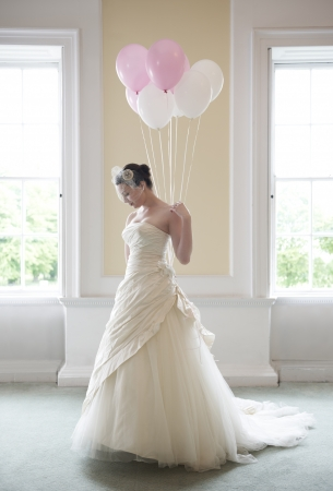 pretty bride in her wedding dress holding ballons in front of windows photo