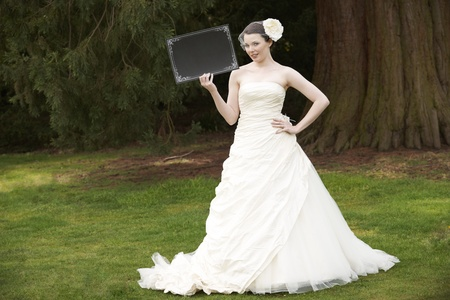 Pretty bride in wedding dress holding a blank board with space for copy Stock Photo
