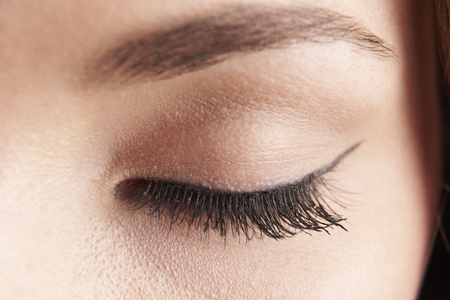 eyes shut: close up of womans brown eye lid with false eye lashes
