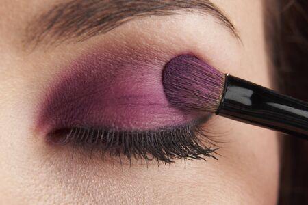 'eyes shut: woman applying eye make-up with brush on white background Stock Photo