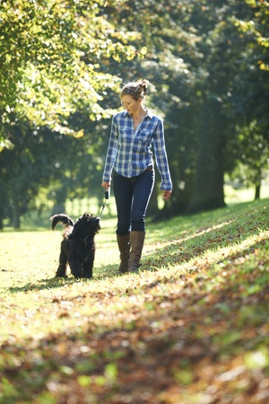woman walking her black dog in the park on a sunny day photo