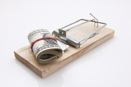 several dollar bills with elastic band  set on a mouse-trap