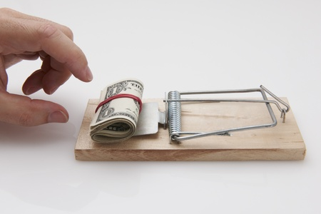 Male hand taking rolled up dollar bills from mousetrap photo