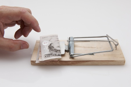 Male hand taking fifty pound note from mousetrap photo