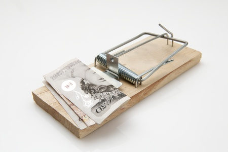 fifty pound note set on a mousetrap on white background photo