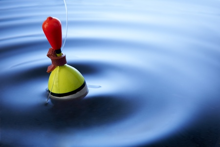 multi coloured fishing float bobbing in water making ripples photo